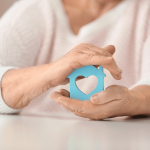 Senior Housing Training An Senior woman is holding a blue house cut out with a heart in her hands